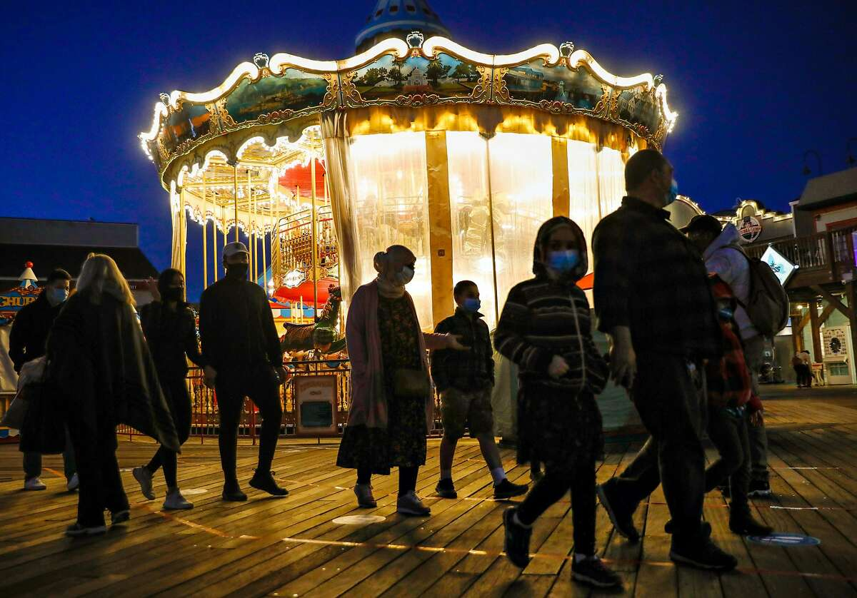 Tourists pass by the carousel at Pier 39 at dusk in November. Despite a surge in COVID-19 cases, hundreds of tourists came to visit Pier 39.