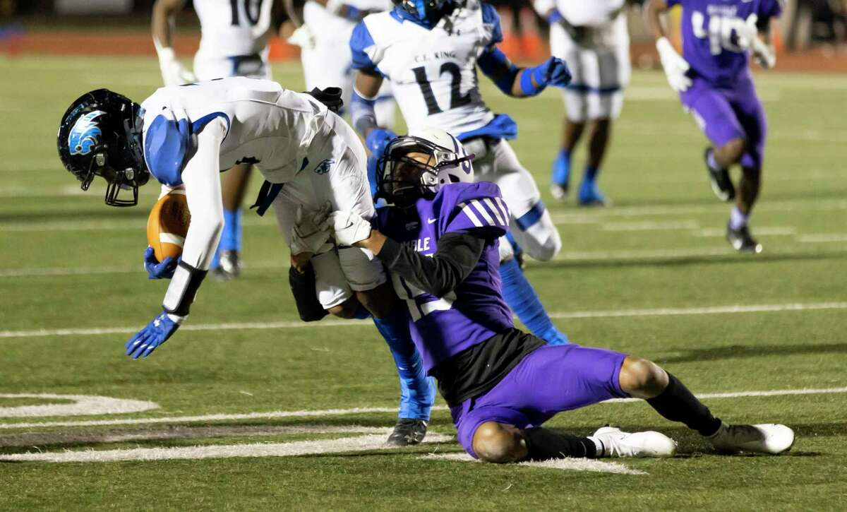 C.E. King wide receiver Eric Adams (3) is grabbed down by Humble defensive back Avory Coleman (15) during the second quarter of a District 21-6A football game at Turner Stadium, Thursday, Dec. 3, 2020.