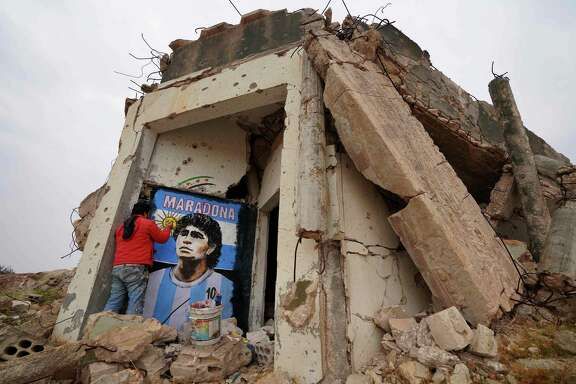 Syrian painter Aziz Asmar creates a mural on the wall of a destroyed home of famous Argentine footballer Diego Maradona, who died Nov. 25 in Tigre, Argentina. Asmar did his mural in the town of Binnish, in Syria's northwestern Idlib province.
