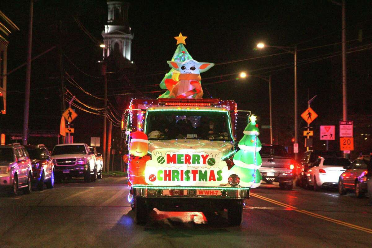 The Danbury Fire Department trucks make their way through downtown Danbury to celebrate the start of the Christmas holiday after a tree lighting at the Danbury Public Library in downtown Danbury, Conn., on Friday Dec. 4, 2020. The coronavirus pandemic forced the event to be scaled down and shown online.