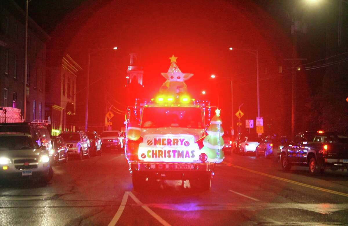 Danbury Fire Department trucks make their way through downtown Danbury to celebrate the start of the Christmas holiday after a tree lighting at the Danbury Public Library in downtown Danbury, Conn., on Friday Dec. 4, 2020. The coronavirus pandemic forced the event to be scaled down and shown online.