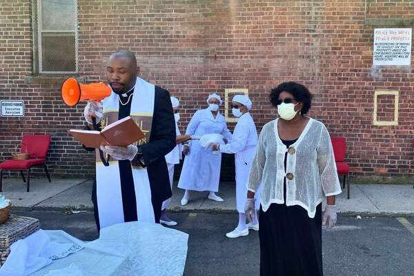 The Rev. Kelcy Steele, left, pastor of Varick Memorial AME Zion Church in New Haven, conducts a drive-through Communion in September 2020.