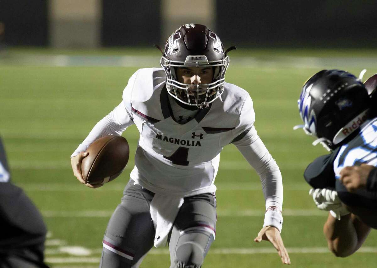Magnolia quarterback Travis Moore (4) looks for an opening to score a touchdown near the endzone during the third quarter of a District 8-5A (Div. I) football game against Magnolia at Randall Reed Stadium in New Caney.
