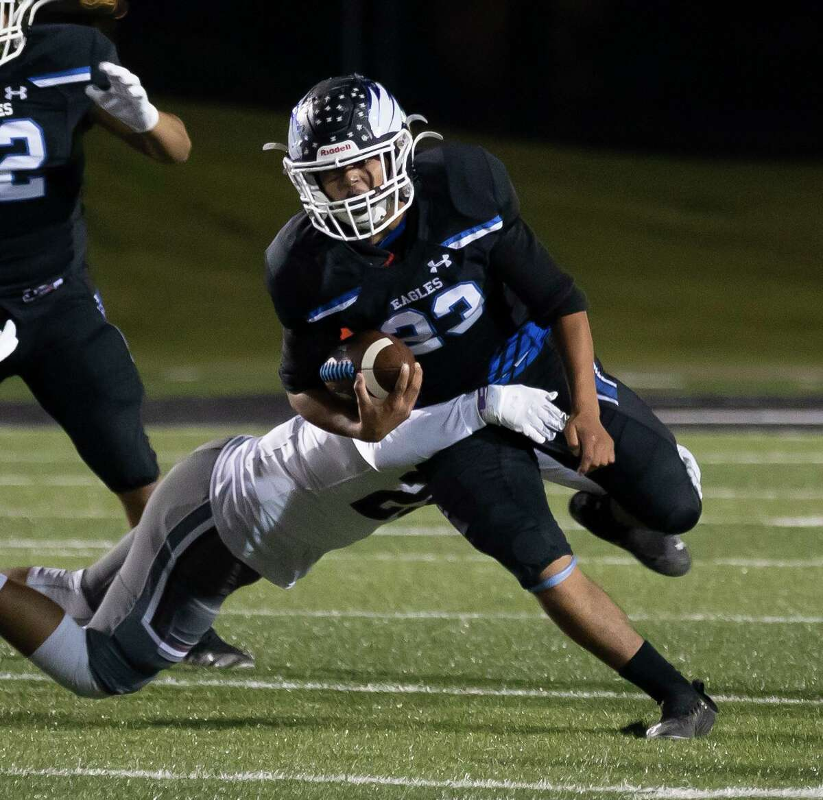 New Caney running back Sebastian Garza (23) is tackled by Magnolia linebacker Eliel Sandoval (25) during the first quarter of a District 8-5A (Div. I) football game at Randall Reed Stadium in New Caney.