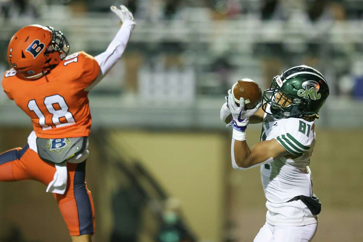 Reagan's Derrick Bohler, right, hauls in a 41-yard touchdown pass over Brandeis' Ramon Bustillos during the first half of their District 28-6A high school football game at Farris Stadium on Friday, Dec. 4, 2020.