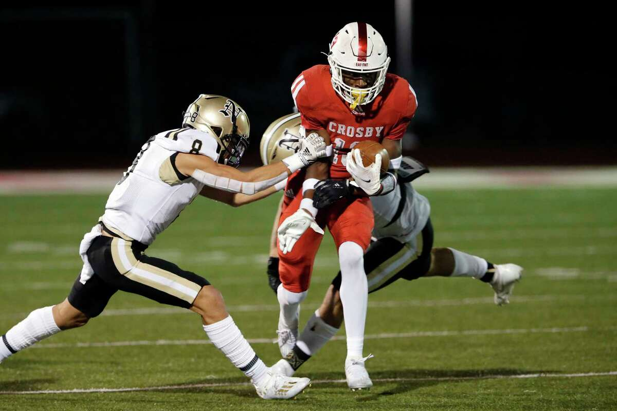 Crosby receiver E'Monte Wilson, middle is caught by Nederland's Kyndon Fuselier (8) and Jaice Beck, back, during the first half of a high school football game at Crosby Cougar Stadium, Friday, Dec. 4, 2020 in Crosby, TX.