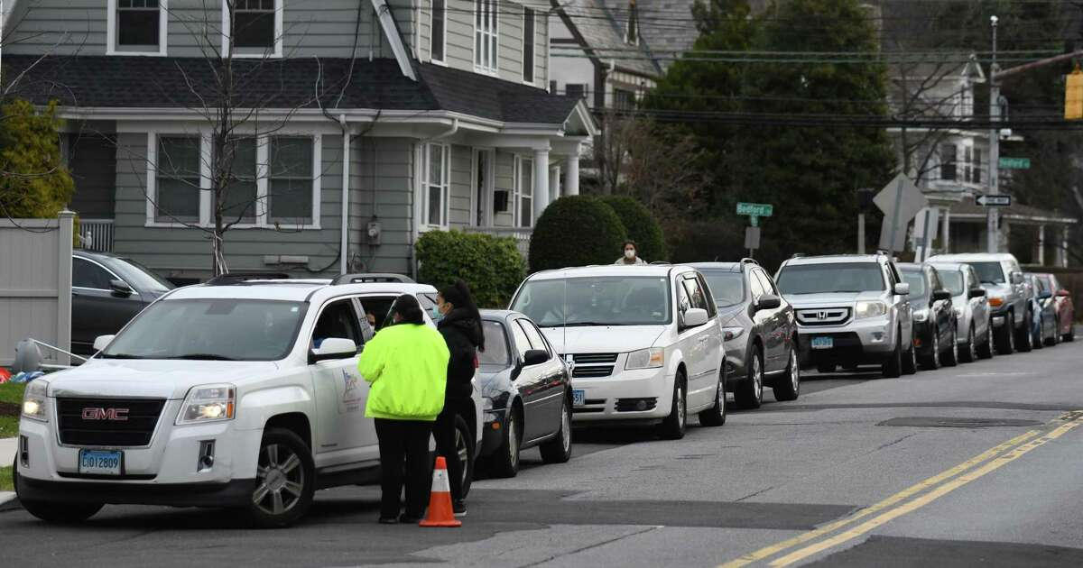 A line of cars stretches down the block as patients wait in their cars to be tested for COVID-19 at Community Health Center in Stamford, Conn. Wednesday, Dec. 2, 2020. Community Health Center's COVID-19 testing line has stretched around the block with patients often waiting several hours.