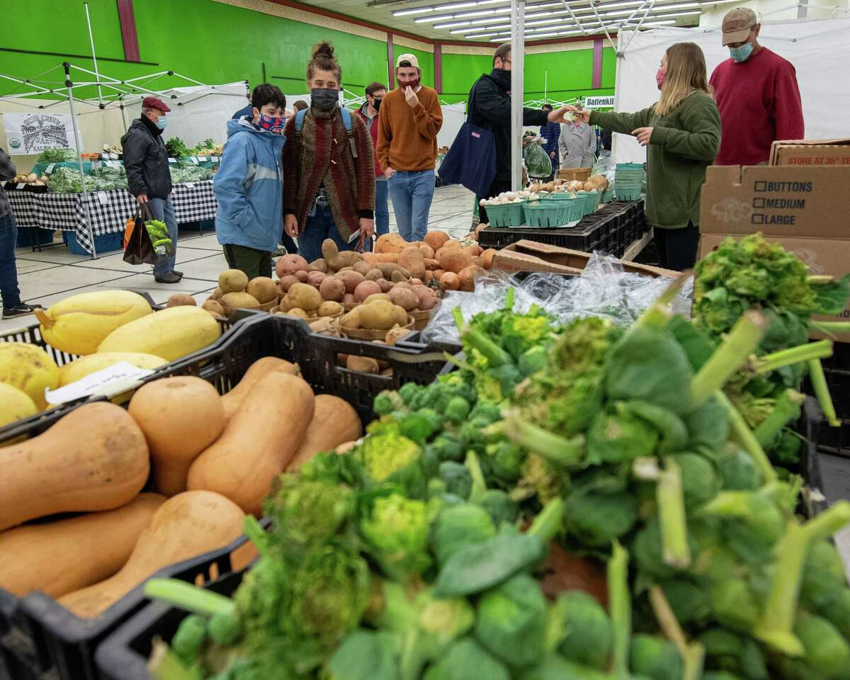 Shoppers peruse fresh vegetables at the Bulich Creekside Farm stand during the first day of the winter Troy Farmers Market at its temporary home in the old Price Chopper Building on Second Avenue in Lansingburgh on Saturday, Dec. 5, 2020 (Jim Franco/special to the Times Union.)