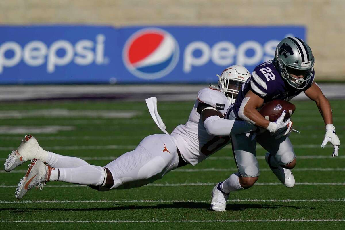 Kansas State running back Deuce Vaughn (22) is tackled by Texas linebacker DeMarvion Overshown, left, during the first half of an NCAA college football game in Manhattan, Kan., Saturday, Dec. 5, 2020. (AP Photo/Orlin Wagner)
