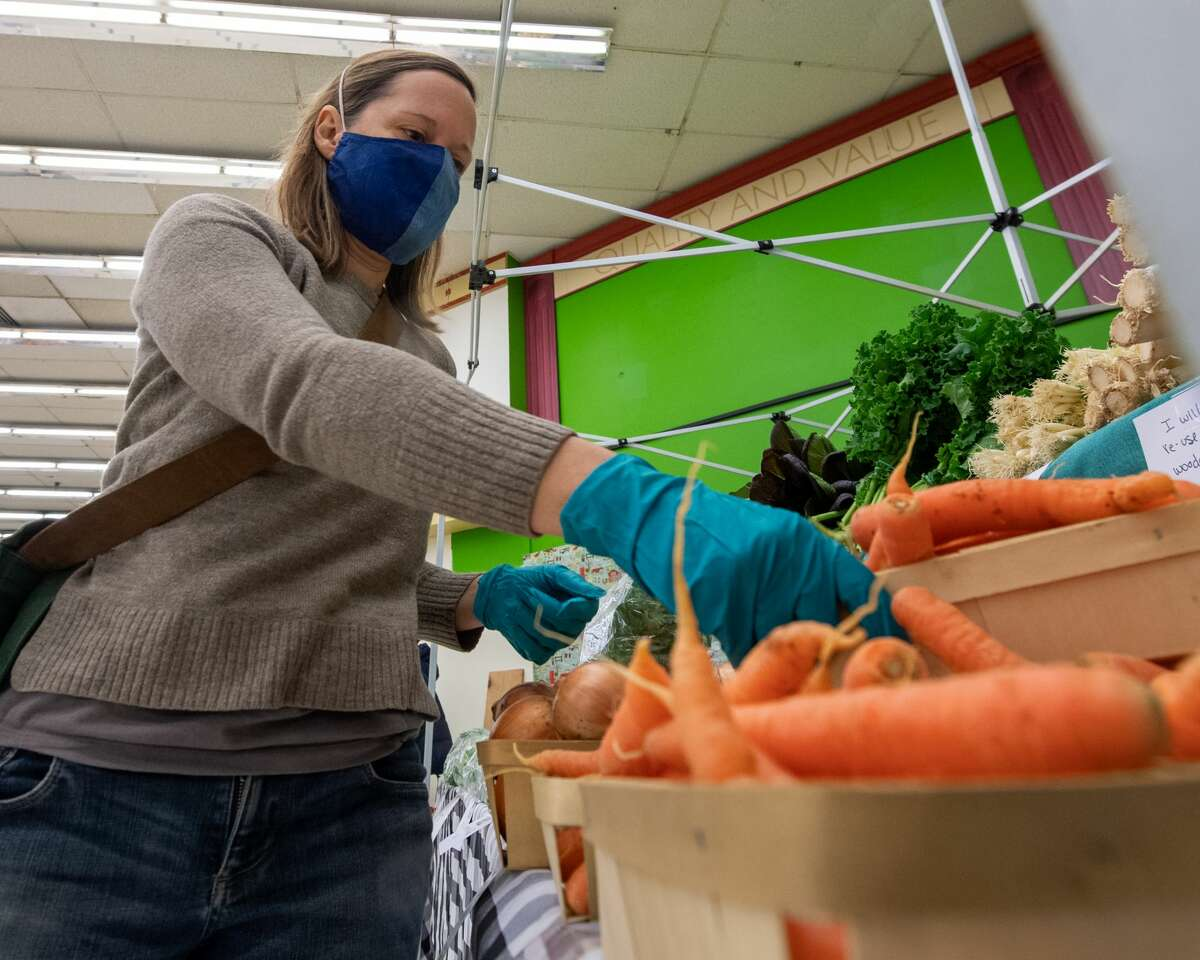 Jennifer Palulis, of Echo Creek Farm, stocks her shelfs during the first day of the winter Troy Farmers Market at its temporary home in the old Price Chopper Building on Second Avenue in Lansingburgh on Saturday, Dec. 5, 2020 (Jim Franco/special to the Times Union.)