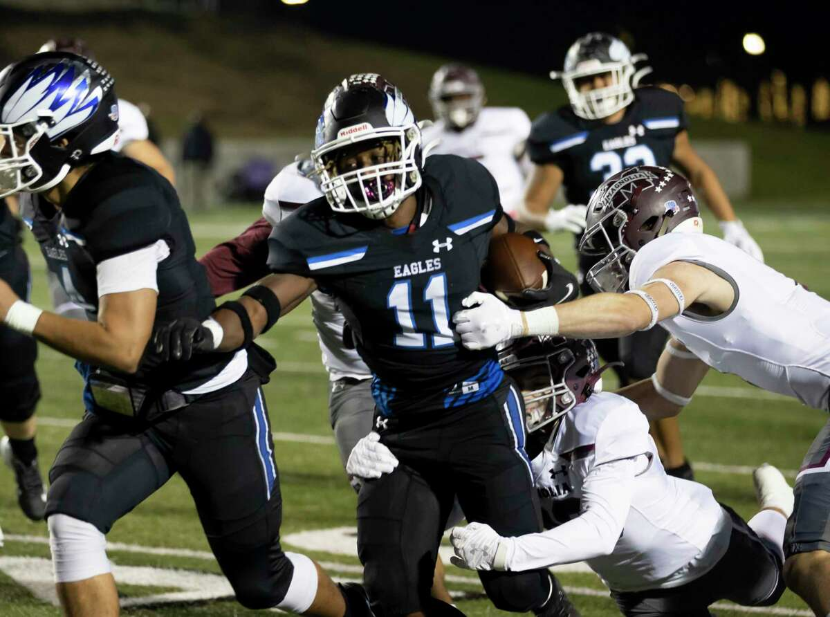 New Caney running back Cale Sanders Jr. (11) attempts to break through the Magnolia defense during the first quarter of a District 8-5A (Div. I) football game at Randall Reed Stadium in New Caney.