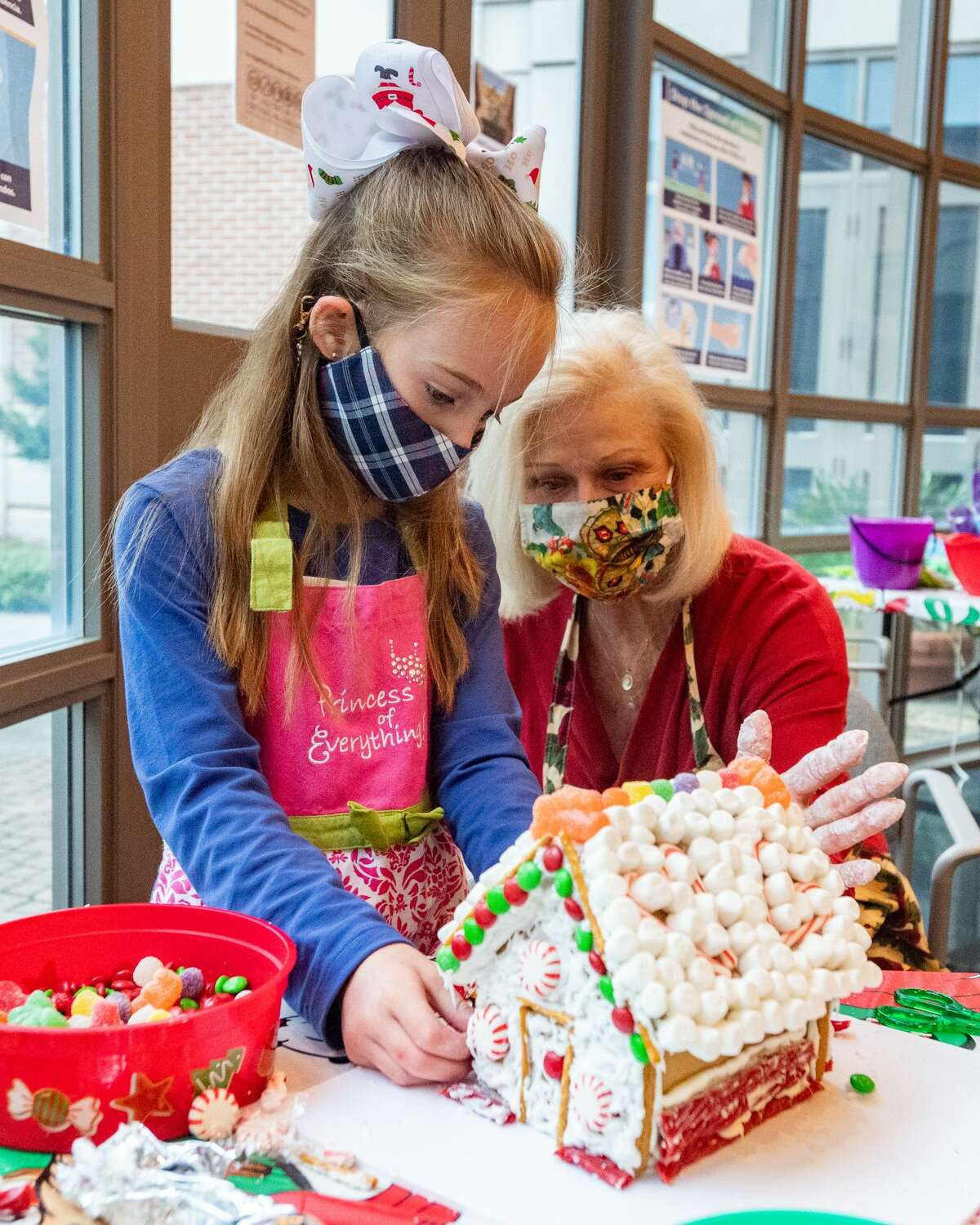 Viviaine Ohmstede, 7, and Kit Ohmstede work on putting some finishiing touches on their log cabin gingerbread house. The Art Museum of Southeast Texas held their our Annual Holiday Gingerbread House Workshop on Saturday, allowing participants to create their very own gingerbread house to add to their home's holiday decor. Photo made on December 5, 2020. Fran Ruchalski/The Enterprise