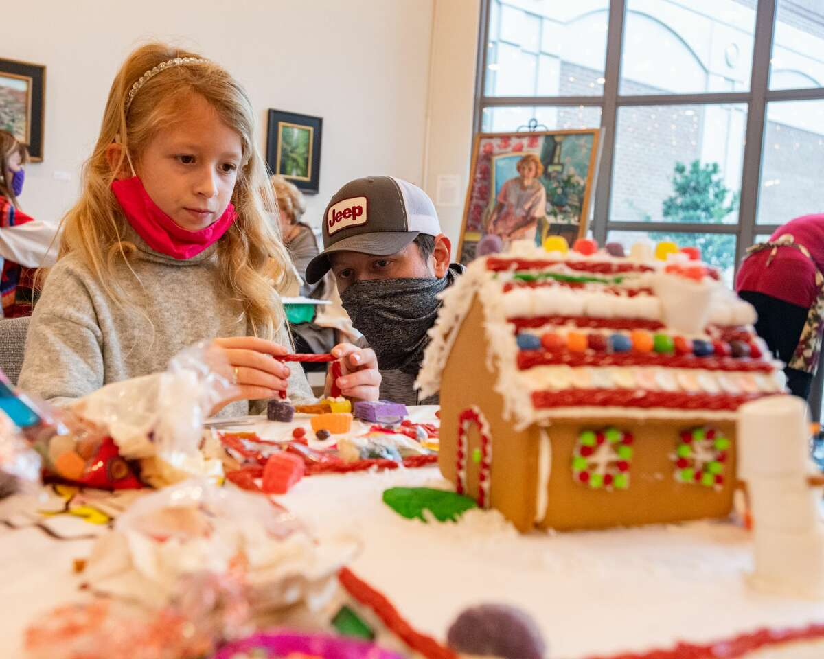 Tinsley Williams, 8, and her dad, Cash Williams contemplate how they can add a bench to their gingerbread house. The Art Museum of Southeast Texas held their our Annual Holiday Gingerbread House Workshop on Saturday, allowing participants to create their very own gingerbread house to add to their home's holiday decor. Photo made on December 5, 2020. Fran Ruchalski/The Enterprise