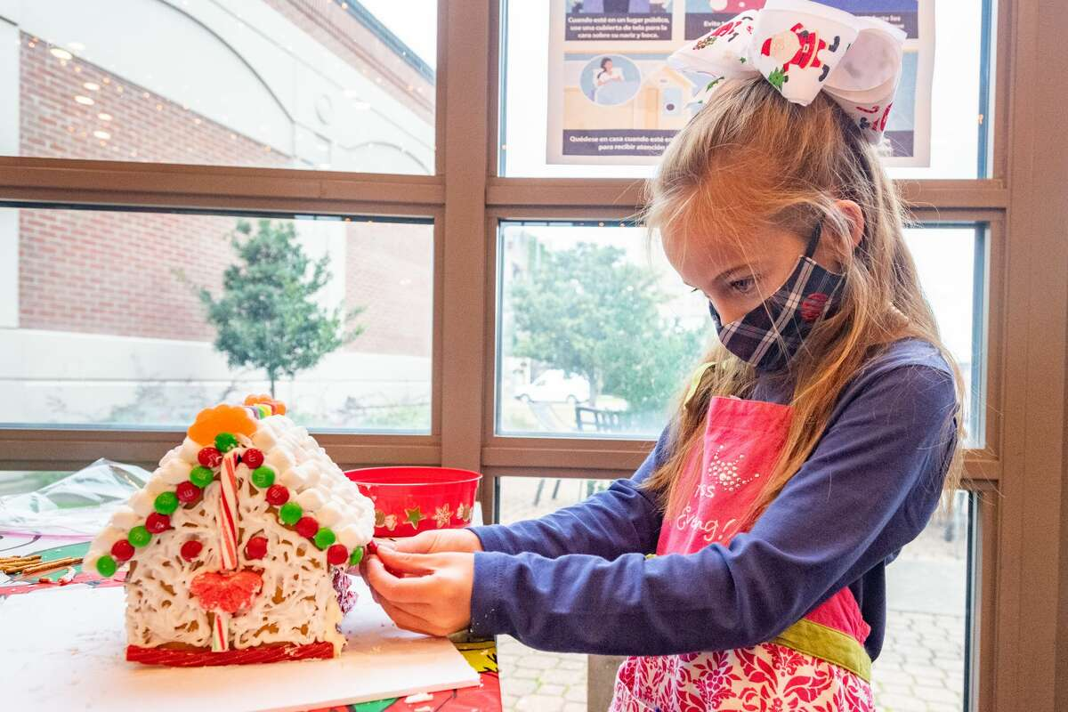 Viviaine Ohmstede, 7, work on putting some finishiing touches on her log cabin gingerbread house. The Art Museum of Southeast Texas held their our Annual Holiday Gingerbread House Workshop on Saturday, allowing participants to create their very own gingerbread house to add to their home's holiday decor. Photo made on December 5, 2020. Fran Ruchalski/The Enterprise