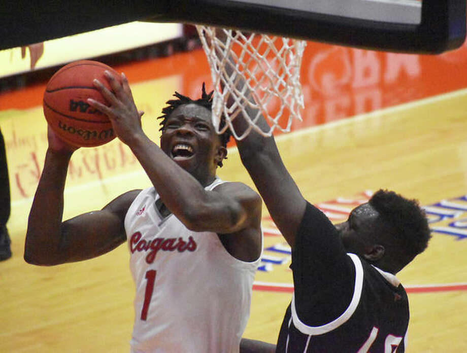 SIUE's Mike Adewumni, left, takes the ball up to the basket while being defended closely by Omaha's Ayo Akinwole in the first half on Saturday in Edwardsville. Photo: Matt Kamp|The Intelligencer