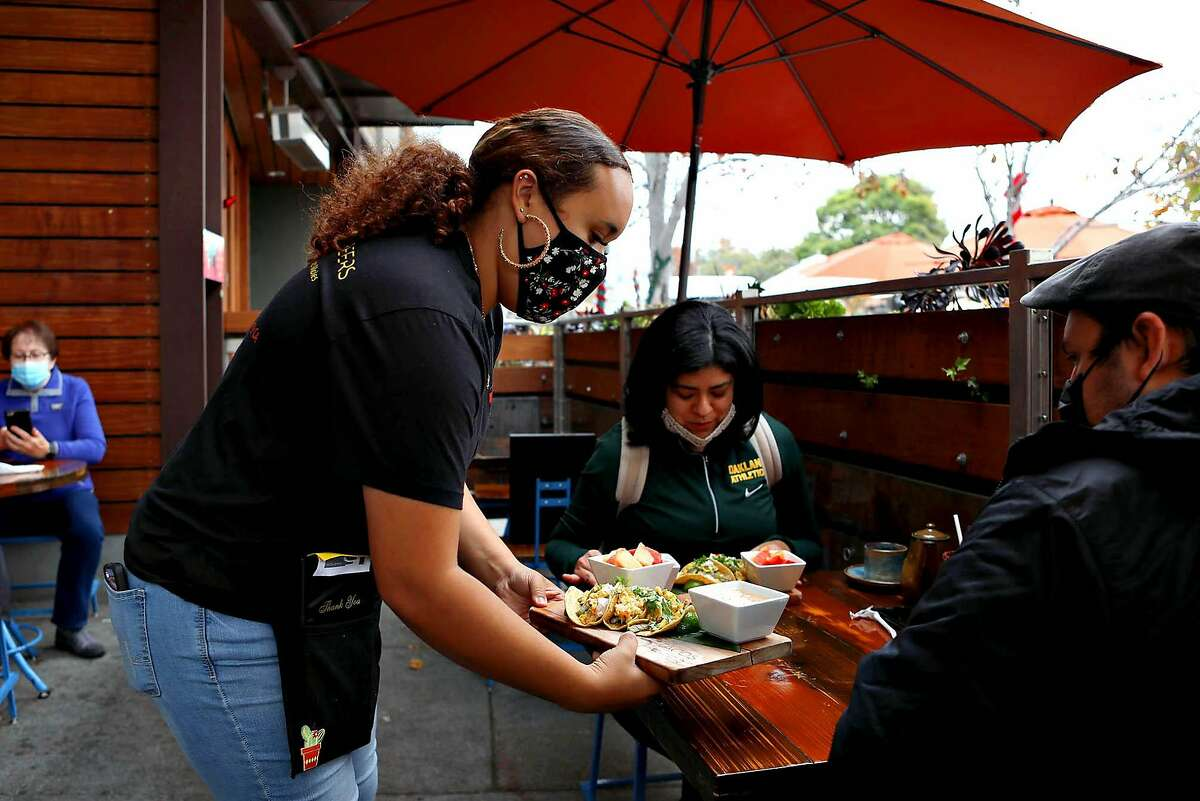 """Server Briselle Lopez delivers food to diners at 5 Tacos and Beers on Solano Ave. on Saturday, December 5, 2020, in Albany, Calif. The Bay Area is expected to go under lockdown and sheltering in place on Sunday. Tipped employees, like servers and bartenders, can be paid as low as $2.13 per hour in some states. The Extra Spicy podcast explores the link between America's tipping culture and the minimum wage debate, and why the fight for fair wages is not just a """"restaurant issue."""""""