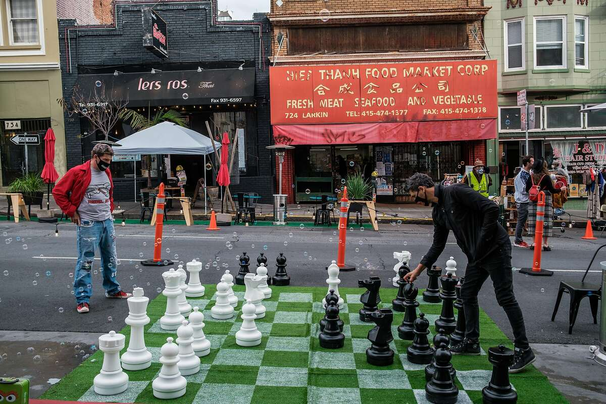 Above: Addison Draper (left) and Tony Velour play chess on Larkin Street in S.F. Left: Visitors look at giraffes at the San Francisco Zoo, which will close Monday under a new stay-home order.