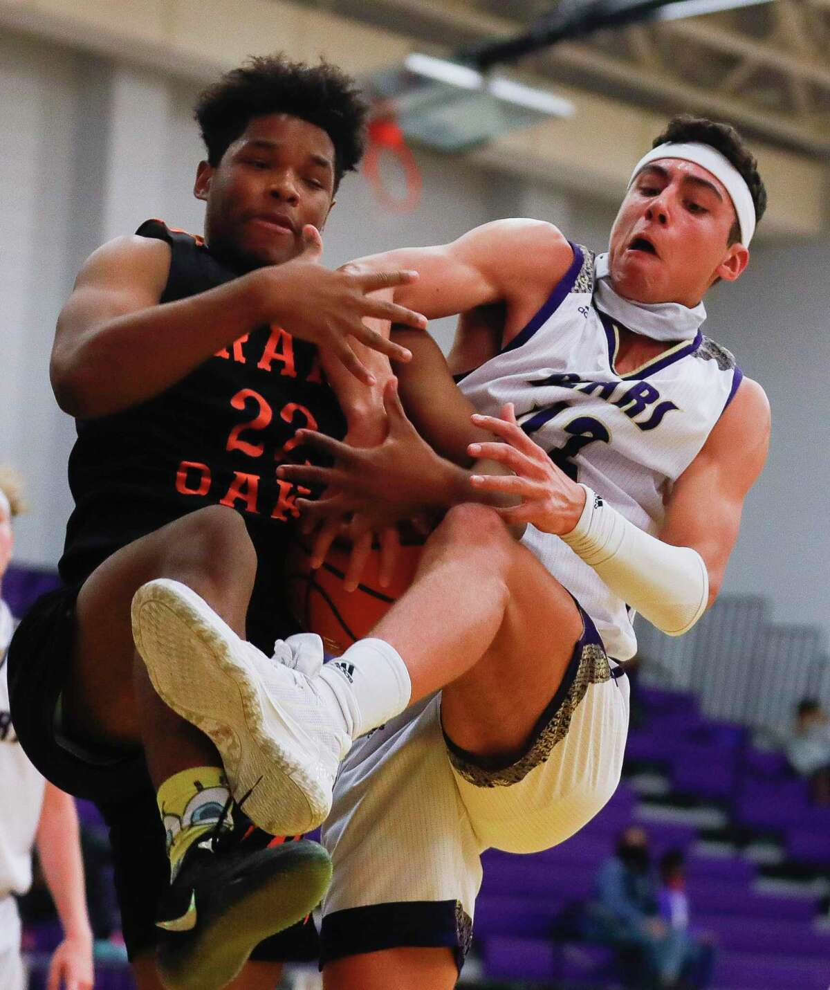 Grand Oaks forward Ian Bayombo (22) battles for a rebound against Montgomery power forward Mateo Moreno (42) during the second quarter of a non-district high school basketball game at Montgomery High School, Saturday, Dec. 5, 2020, in Montgomery.