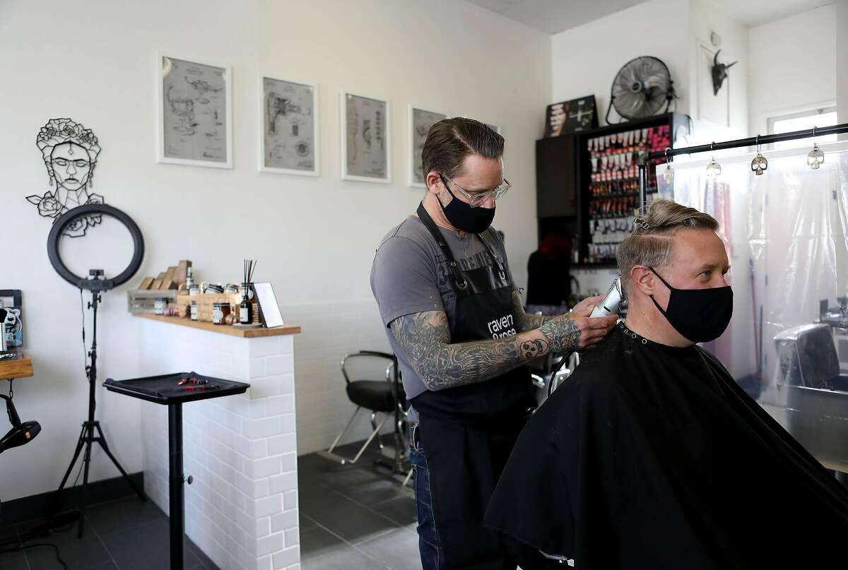 Noel Shabazian, co-owner, cuts Mark Westover's hair inside his hair salon, Raven and Rose, on Saturday in Albany. Many rushed to get haircuts this weekend before the lockdown.