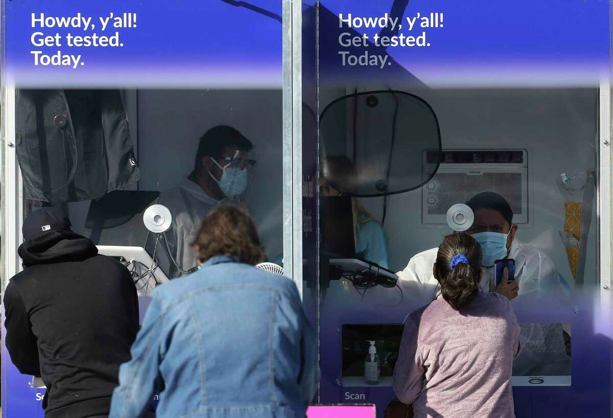 People line up for COVID-19 tests at a free popup site at the Edgewood Square shopping center on South General McMullen Drive, Friday, Dec. 4, 2020.