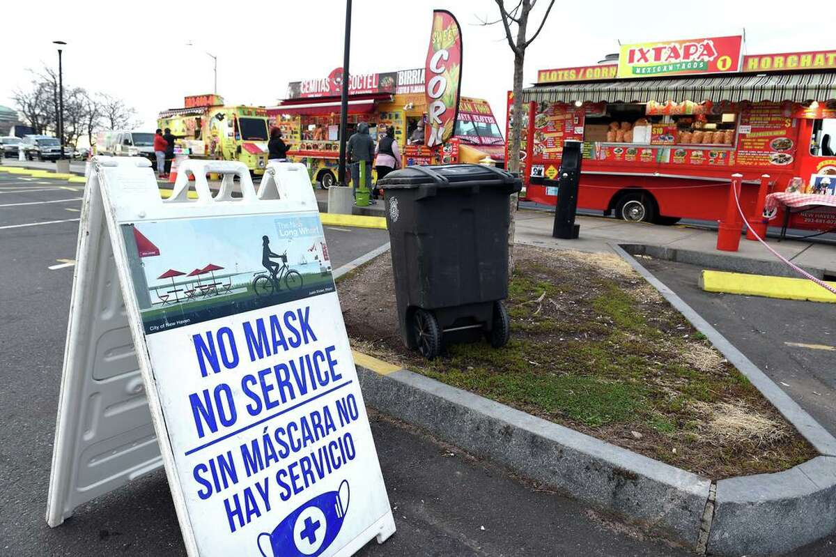 NO MASK NO SERVICE signs are displayed at the food truck area on Long Wharf Drive in New Haven on December 4, 2020.