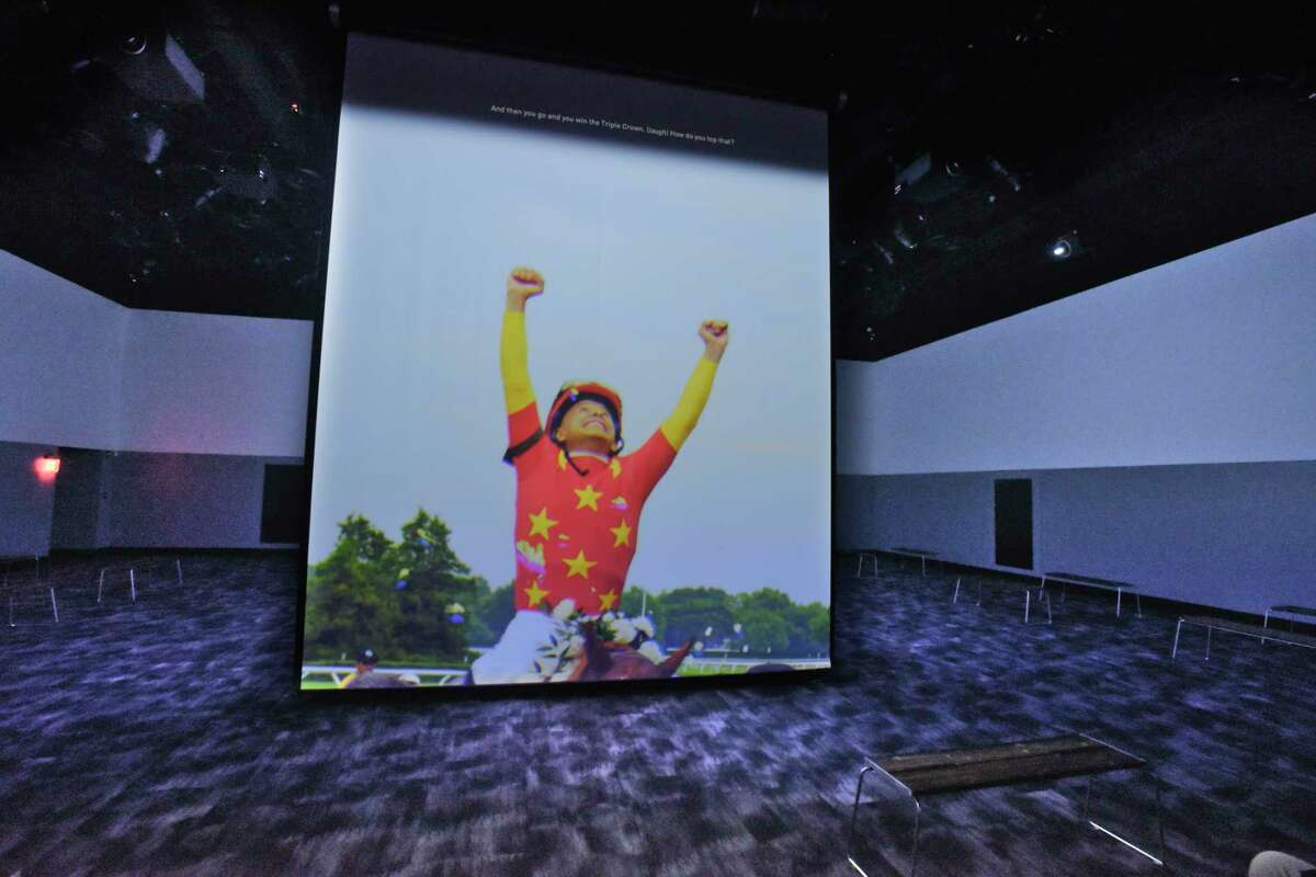 """The film, """"What it Takes: Journey to the Hall of Fame"""", plays on the screen in the Hall of Fame at The National Museum of Racing and Hall of Fame on Thursday, Dec. 3, 2020, in Saratoga Springs, N.Y. (Paul Buckowski/Times Union)"""