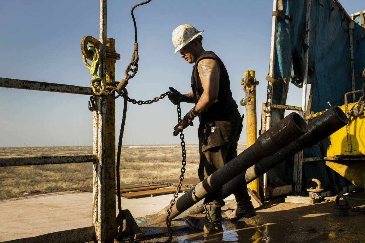 A worker prepares to lift drills by pulley to the main floor of Endeavor Energy Resources LP's Big Dog Drilling Rig 22 in the Permian basin outside of Midland in this 2014 file photo.
