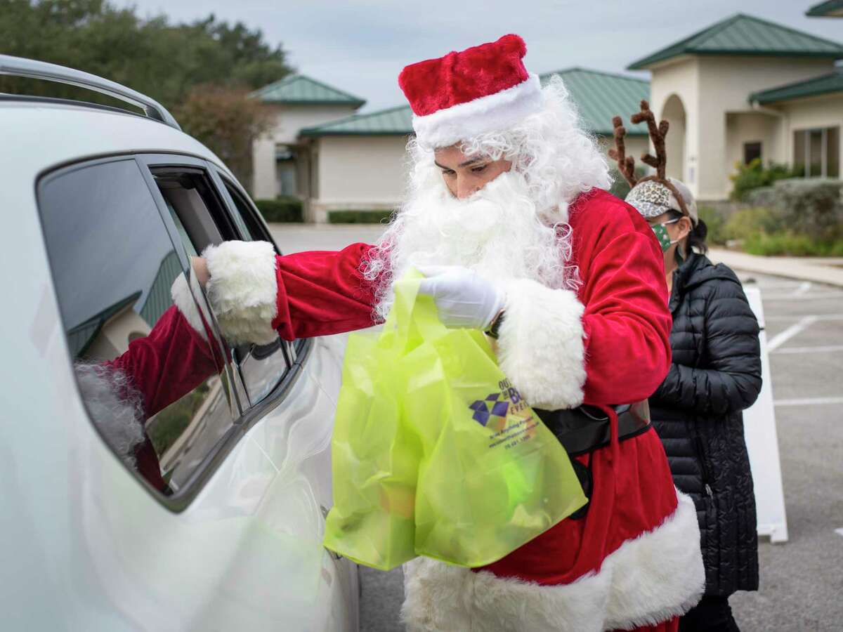 Samuel Neuman volunteering as Santa Claus, and his mother Amanda Neuman, right, deliver holiday swag bags to visitors as part of the Baptist Health System?•s virtual Winterfest celebration via Zoom on Saturday, December 5, 2020 in San Antonio, Tx., U.S.