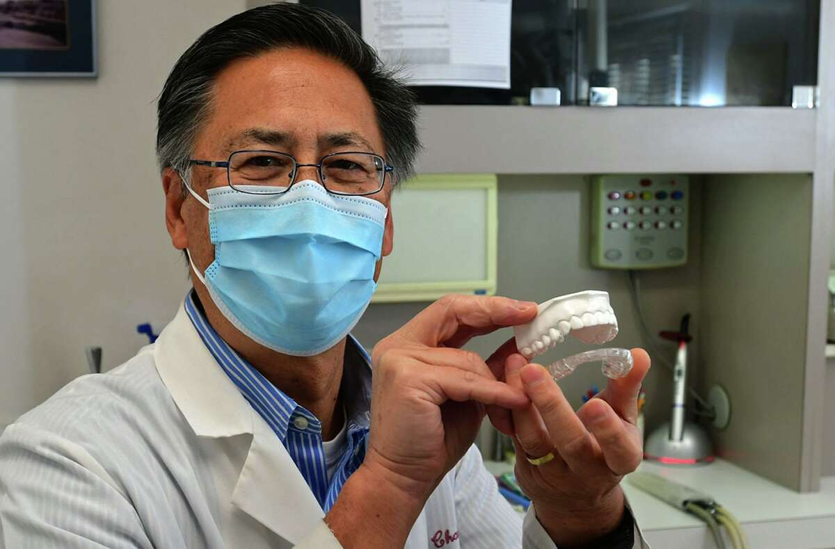 Dr. Greg Chann holds a model of teeth at his Wilton office.