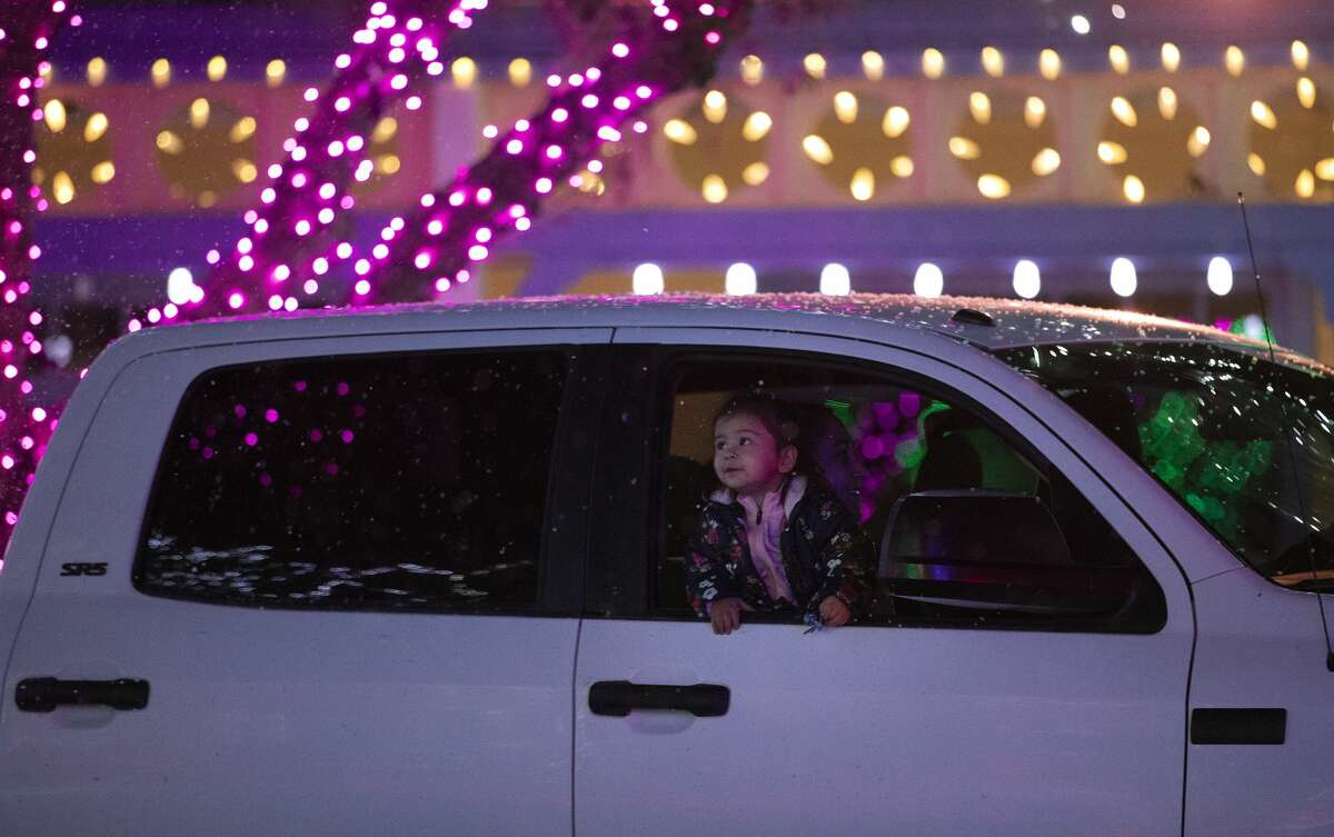 A young visitor looks out at the falling snow and colorful lights at Six Flags Magic Mountain. The holiday drive-through event is to help make up for the revenue lost by the closure of the theme park. The drive-through is open daily until January 3, 2021, unless health department orders force them to close.