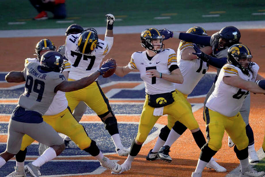 Iowa quarterback Spencer Petras is pressured by Illinois defensive lineman Owen Carney Jr. (99) and Roderick Perry II during the first half of an NCAA college football game Saturday, Dec. 5, 2020, in Champaign, Ill. Photo: Associated Press
