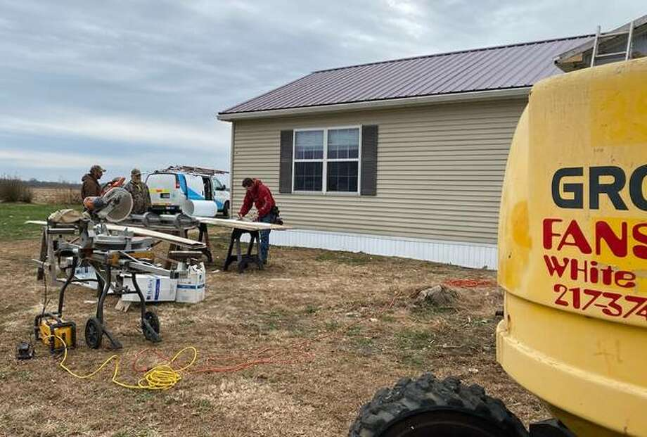 Volunteers complete exterior work on Janet Coonrod's home in Barrow. Several of the Coonrod's neighbors joined forces this fall to get her into her new handicap-accessible home.