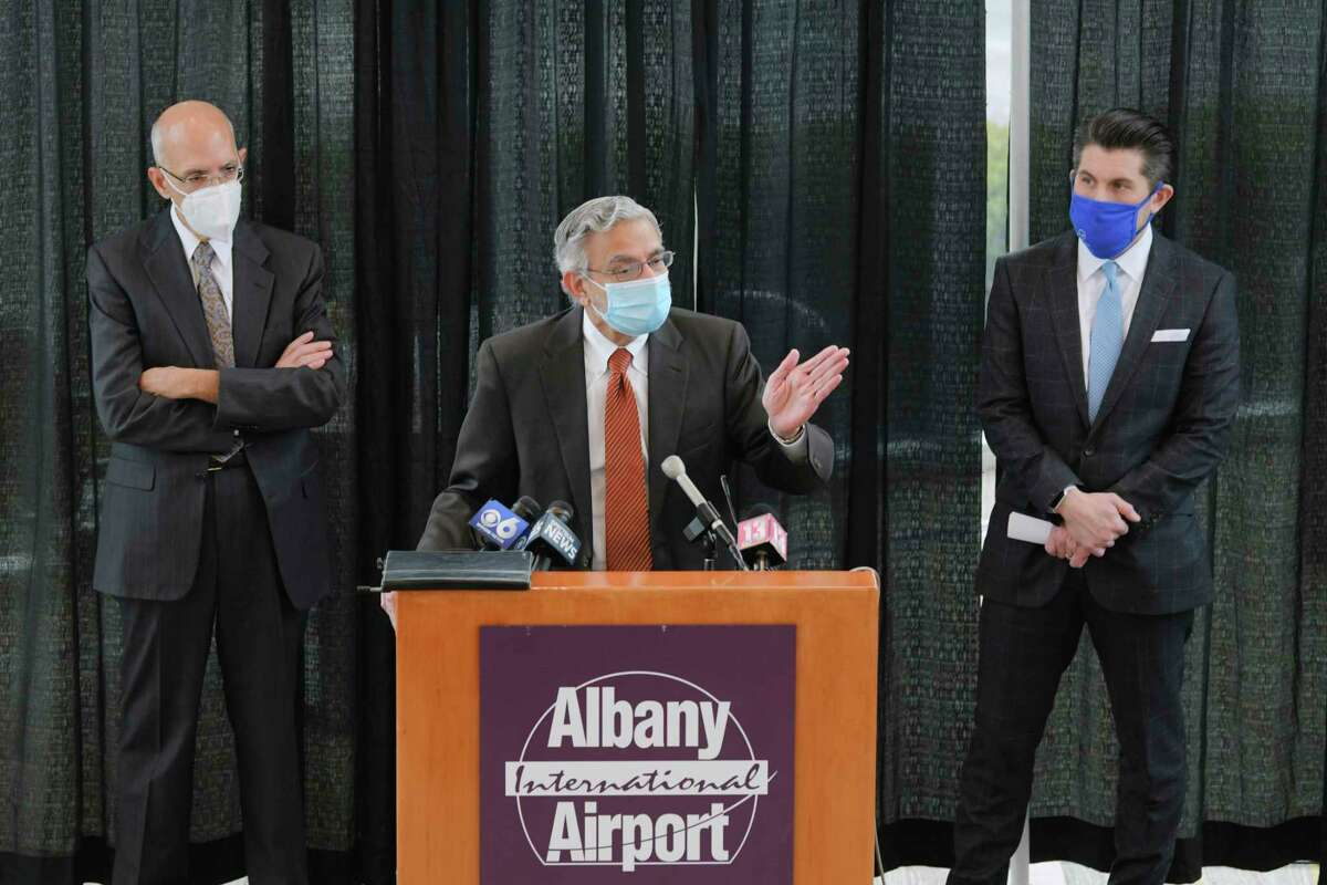 SUNY Upstate Medical President Mantosh Dewan, center, speaks at a press conference as Albany International Airport CEO Philip Calderone, left, and State University of New York Chancellor Jim Malatras, right, look on, at the airport on Sunday, Dec. 6, 2020, in Colonie, N.Y. It was announced at the press conference that that a saliva test developed at SUNY Upstate Medical University is planned to be used to test all airport employees and ultimately be available to passengers for a fee. (Paul Buckowski/Times Union)