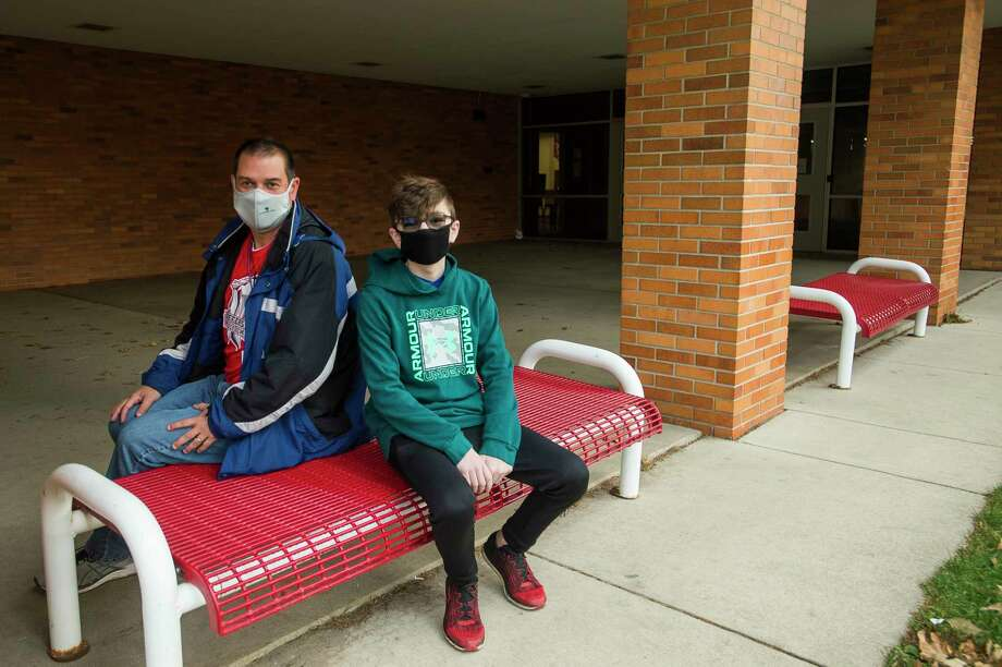 Brent Doty, a teacher at Jefferson Middle School, left, and Landon Stanford, a sixth-grade student, pose for a portrait Friday morning in front of the school. Doty performed lifesaving CPR on Stanford on Sept. 17 on the school playground. (Katy Kildee/kkildee@mdn.net)