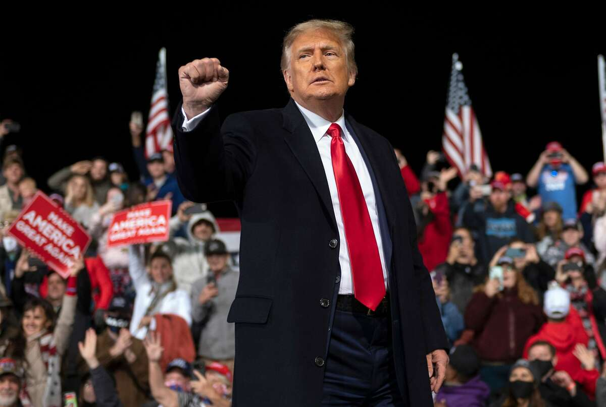 FILE: US President Donald Trump holds up his fist as he leaves the stage at the end of a rally to support Republican Senate candidates at Valdosta Regional Airport in Valdosta, Georgia on December 5, 2020.