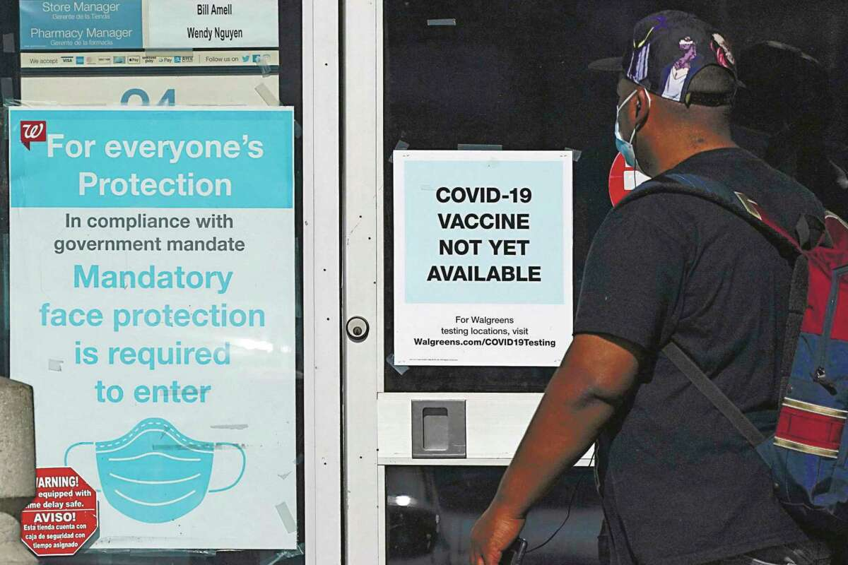 In this Dec. 2, 2020, file photo, a customer walks past a sign indicating that a COVID-19 vaccine is not yet available at Walgreens in Long Beach, Calif. (AP Photo/Ashley Landis)