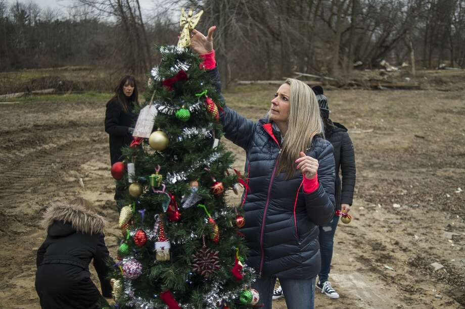 Crystal Kerns places a star on top of the tree Sunday, Dec. 6, 2020 as members of her family help decorate a Christmas tree where her home once stood in downtown Sanford, before it was destroyed by the dam failures and flood in May. (Katy Kildee/kkildee@mdn.net) Photo: (Katy Kildee/kkildee@mdn.net)