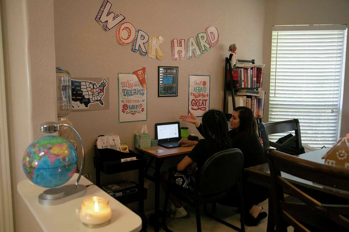 Hannah Sturgis talks with her son, Eden Jackson, 11, a sixth grader at Robert L. Vale Middle School, as he attends classes virtually at their home in San Antonio on Thursday.