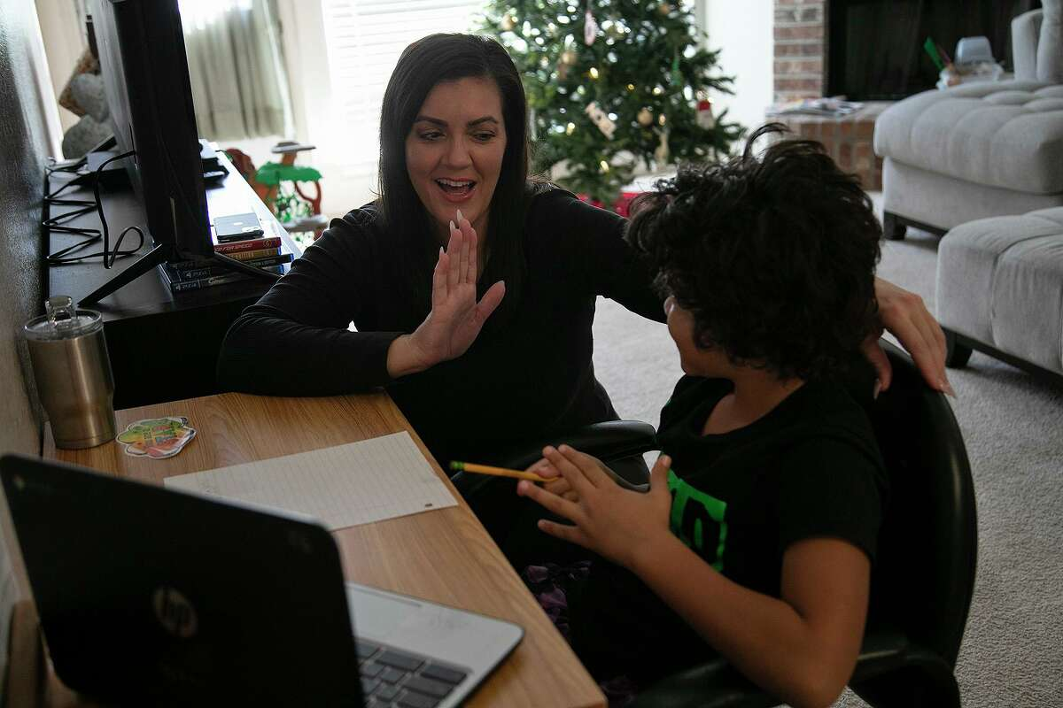 Hannah Sturgis holds up her hand for a high five from her son, Sol Jackson, 8, a third grader at Dr. Winn Murnin Elementary School, as he attends classes virtually at their home in San Antonio.