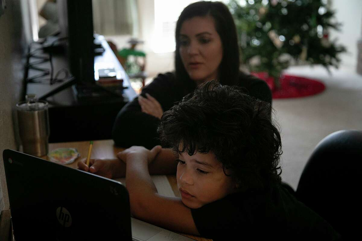 Hannah Sturgis watches her son, Sol Jackson, 8, a third grader at Dr. Winn Murnin Elementary School, as he attends a class virtually at their home in San Antonio on Dec. 3.