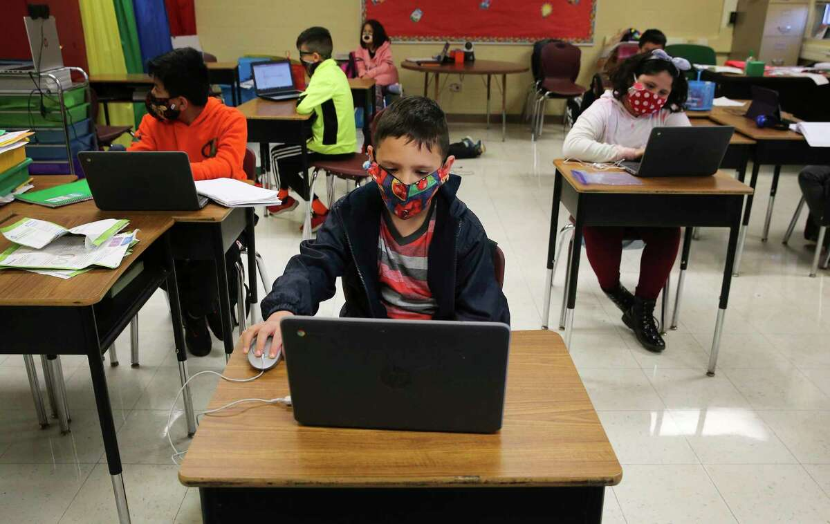 Third-grader Masyn Uriegas (front) joins other students in class at Pearce Elementary at Southside ISD on Dec. 3. Students there attend a combination of online and in-person classes.