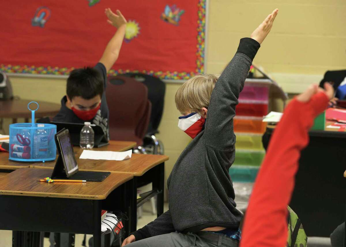 Third-grader Logan Sapp (center) raises his arm to answer a question as students at Pearce Elementary at Southside ISD attend a combination of online and in-person class learning on Thursday, Dec. 3, 2020. According to Southside ISD Director of PR and Community Randy Escamilla, about half of the elementary school are currently in school and the other half are online as a result of the Coronavirus pandemic.