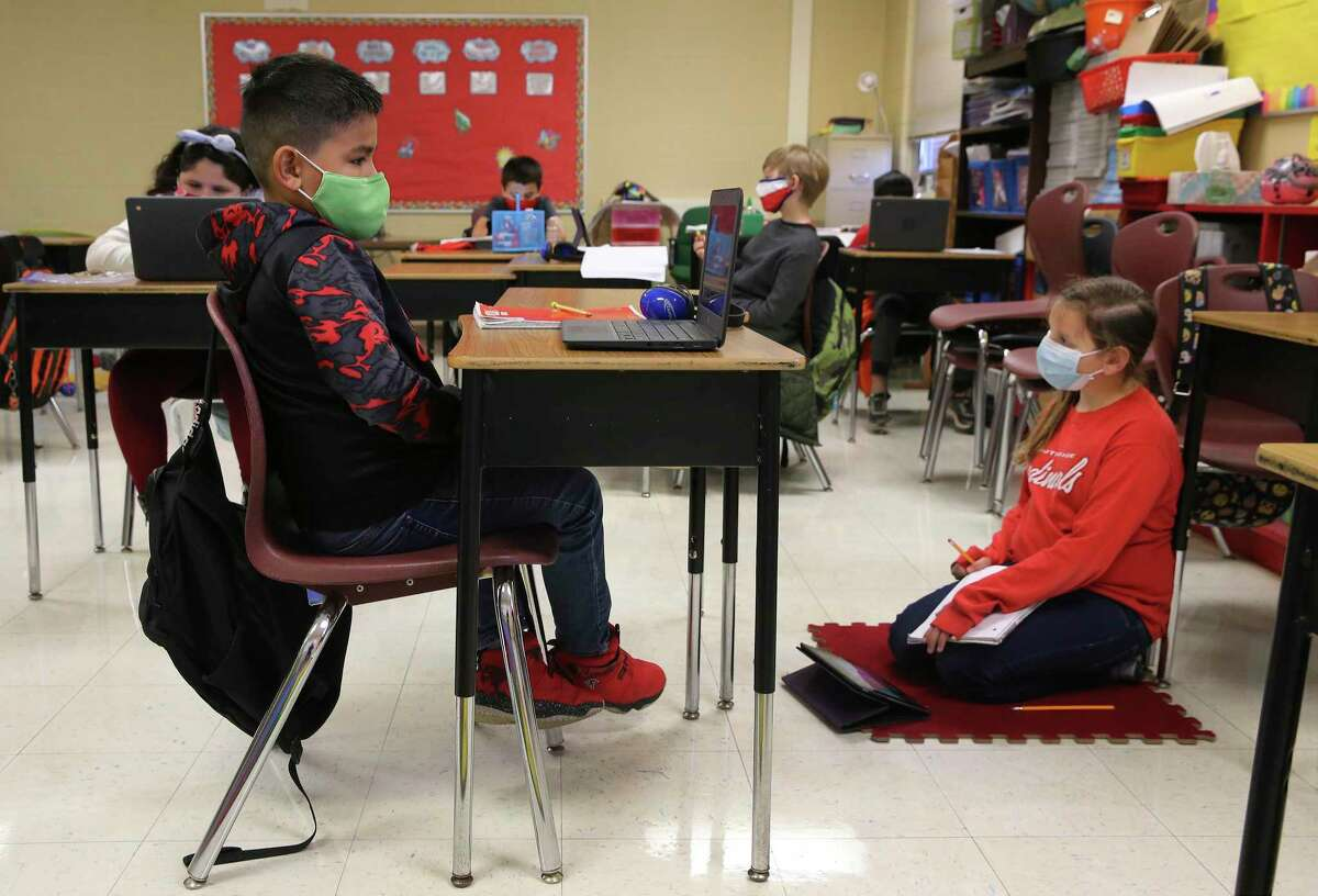 Third-graders Aaron Diaz (left) and Naomi Castro take part in a class lesson as students at Pearce Elementary at Southside ISD attend a combination of online and in-person class learning on Thursday, Dec. 3, 2020.