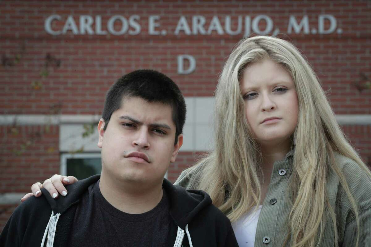 Carlos Araujo-Preza Jr., and his sister, Andrea, stand outside of their father's Dr. Carlos Araujo-Preza office who died after becoming infected with COVID-19 Saturday, Dec. 5, 2020, in The Woodlands.