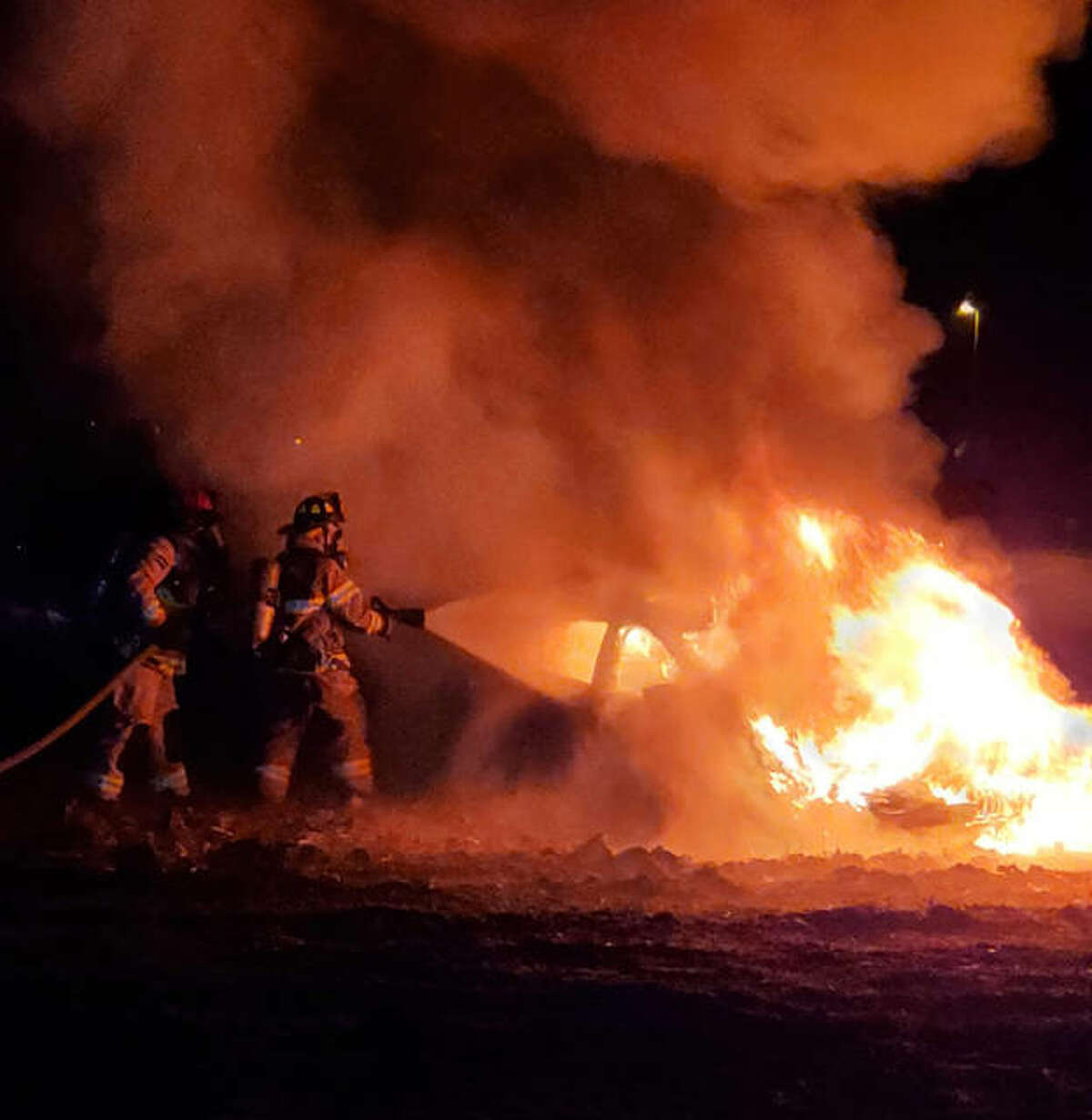 Highland firefighters work to extinguish a car on fire early Sunday morning.