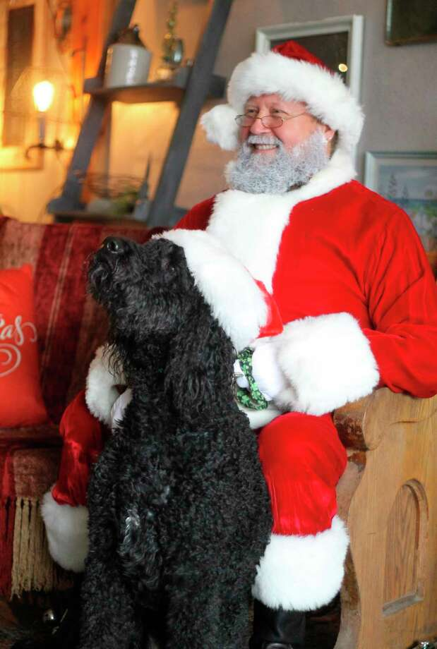 Santa Claus poses with a dog in Patina Designs in Onekama as part of a fundraiser sponsored by Patina, Anchored Designs and Yellow Dog Cafe on Sunday. Lori Wilson of Lori Wilson Photography was on hand to take pet portraits. Proceeds from the event go to Homeward Bound Animal Shelter. (Kyle Kotecki/News Advocate)