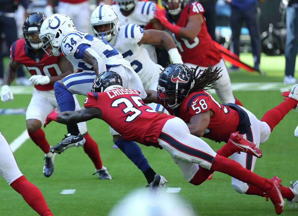 Indianapolis Colts cornerback Isaiah Rodgers (34) leaps as he is hit by Houston Texans linebacker Peter Kalambayi (58) and cornerback Keion Crossen (35) for extra yardage returning a kick during the first half of an NFL football game at NRG Stadium on Sunday, Dec. 6, 2020, in Houston.