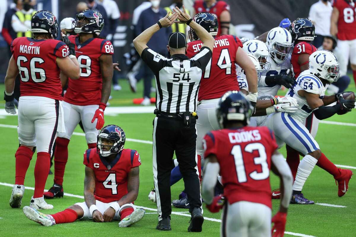 Houston Texans quarterback Deshaun Watson (4) sits on the turf as Indianapolis Colts middle linebacker Anthony Walker (54) runs off the field with the football after recovering Watson's fumble near the goal line during the fourth quarter of an NFL football game at NRG Stadium on Sunday, Dec. 6, 2020, in Houston.