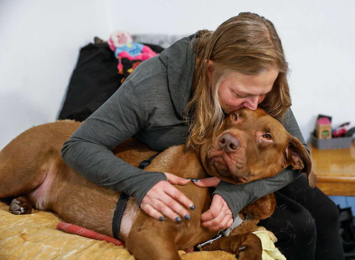 Jenn Oakley, who was previously homeless, cuddles her dog Fattie in her new studio apartment on Tuesday, Dec. 1, 2020 in Berkeley, California.This is the first time she�s had a place of her own in twelve years.