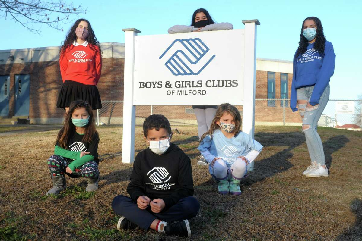 Seated front, Thomas Marder, kneeling left and right, Lucia Garcia and Mirella Soto, and standing left to right Lissette Soto, Alexis Broderick and Tiffany Ialeggio pose in front of Milford Boys & Girls Clubs, in Milford, Conn. Dec. 3, 2020.